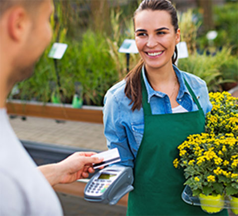 Man using credit card to purchase potted flowers from woman
